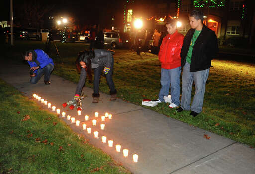 Stratford High School student Eva Juarez places a few roses in front of a candle memorial put together by Nancy and and her partner Nicki Orengo, at right, as hundreds attend a candlelight vigil in memory of victims from yesterday's mass shooting in Newtown, which was held behind Stratford High School on the Town Hall Green in Stratford, Conn. on Saturday December 15, 2012. Photo: Christian Abraham / Connecticut Post
