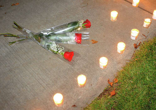 Stratford High School student Eva Juarez placed these roses in front of a candle memorial made by Nancy and and her partner Nicki Orengo, as hundreds attend a candlelight vigil in memory of victims from yesterday's mass shooting in Newtown, which was held behind Stratford High School on the Town Hall Green in Stratford, Conn. on Saturday December 15, 2012. Photo: Christian Abraham / Connecticut Post