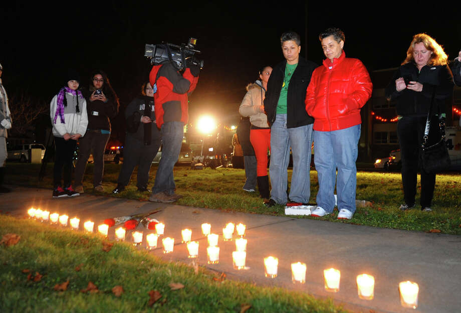 Nancy Orengo and her partner Nicki, at right, look at a candle memorial they laid out on the sidewalk, as hundreds attend a candlelight vigil in memory of victims from yesterday's mass shooting in Newtown, which was held behind Stratford High School on the Town Hall Green in Stratford, Conn. on Saturday December 15, 2012. Photo: Christian Abraham / Connecticut Post