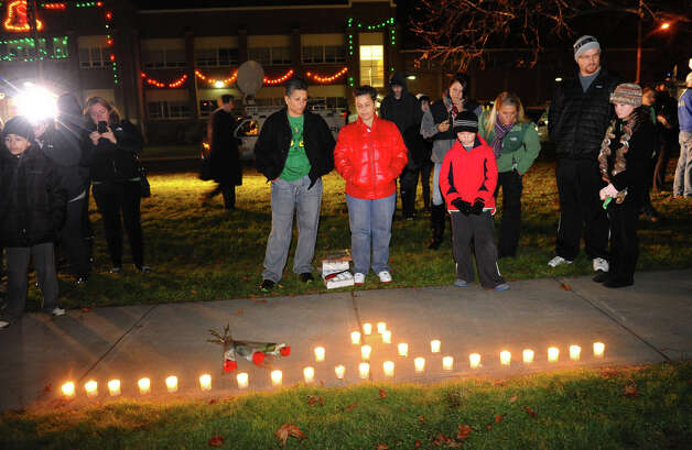 Nancy Orengo and her partner Nicki, at center right, look at a candle memorial they laid out on the sidewalk, as hundreds attend a candlelight vigil in memory of victims from yesterday's mass shooting in Newtown, which was held behind Stratford High School on the Town Hall Green in Stratford, Conn. on Saturday December 15, 2012. Photo: Christian Abraham / Connecticut Post