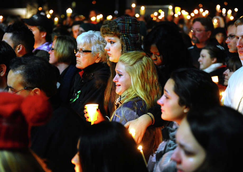 Stratford High School seniors Ally Kutzer and Caitlyn Larocque, center front, attend a candlelight vigil with hundreds of other in memory of victims from yesterday's mass shooting in Newtown, which was held behind Stratford High School on the Town Hall Green in Stratford, Conn. on Saturday December 15, 2012. Photo: Christian Abraham / Connecticut Post