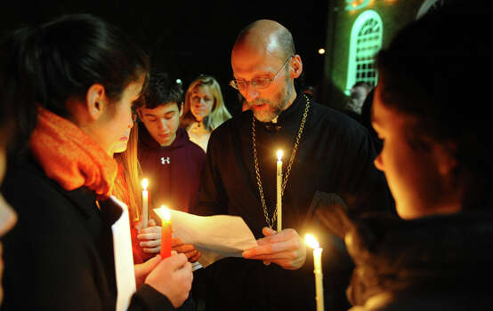 Father Peter Paproski, of St. John's Orthodox Church, offers up a prayer to several people as hundreds attend a candlelight vigil in memory of victims from yesterday's mass shooting in Newtown, which was held behind Stratford High School on the Town Hall Green in Stratford, Conn. on Saturday December 15, 2012. Photo: Christian Abraham / Connecticut Post