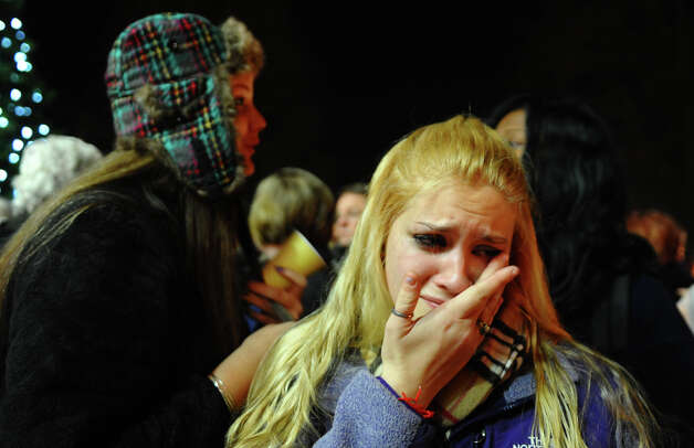 Stratford High School senior Caitlyn Larocque, front, sheds a tear as she and hundreds of others attend a candlelight vigil, in memory of victims from yesterday's mass shooting in Newtown, which was held behind Stratford High School on the Town Hall Green in S
