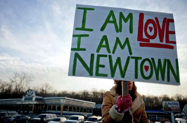 A Newtown, Conn., resident, who declined to give her name, sits at an intersection holding a sign for passing motorists up the road from the Sandy Hook Elementary School, Saturday, Dec. 15, 2012, in Newtown, Conn. The massacre of 26 children and adults at Sandy Hook Elementary school elicited horror and soul-searching around the world even as it raised more basic questions about why the gunman, 20-year-old Adam Lanza, would have been driven to such a crime and how he chose his victims. (AP Photo/David Goldman) Photo: David Goldman