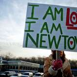 A Newtown, Conn., resident, who declined to give her name, sits at an intersection holding a sign for passing motorists up the road from the Sandy Hook Elementary School, Saturday, Dec. 15, 2012, in Newtown, Conn. The massacre of 26 children and adults at Sandy Hook Elementary school elicited horror and soul-searching around the world even as it raised more basic questions about why the gunman, 20-year-old Adam Lanza, would have been driven to such a crime and how he chose his victims. (AP Photo/David Goldman)