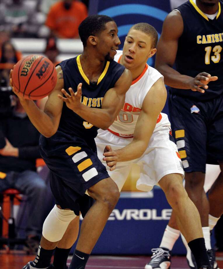 Syracuse's Brandon Triche, right, defends against Canisius' Harold Washington during the first half of an NCAA college basketball game in Syracuse, N.Y., Saturday, Dec. 15, 2012. (AP Photo/Kevin Rivoli) Photo: KEVIN RIVOLI