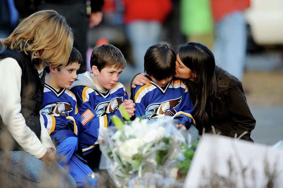 People visit a small memorial set up near Sandy Hook Elementary School on Saturday in Newtown, Conn. Photo: Olivier Douliery, MBR / Abaca Press