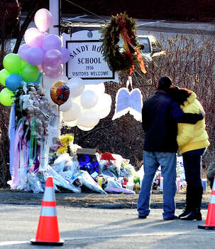 Mourners react after placeing flowers on a memorial built around the sign for the Sandy Hook School in Newtown Saturday, Dec. 15, 2012. Sandy Hook Elementary School was the site of a mass shooting on Friday. Photo: Michael Duffy, The News-Times / The News-Times