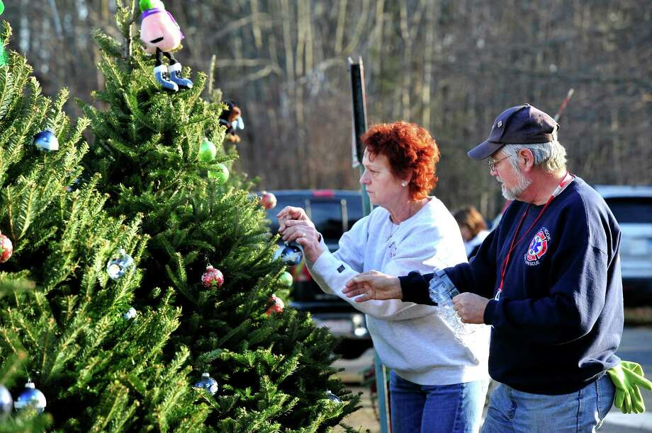Members of the Sandy Hook Volunteer Fire Department decorate Christmas trees along Dickenson Drive leading to the Sandy Hook Elementary School in Newtown Saturday, Dec. 15, 2012. The school was the site of a mass shooting on Friday. Photo: Michael Duffy / The News-Times