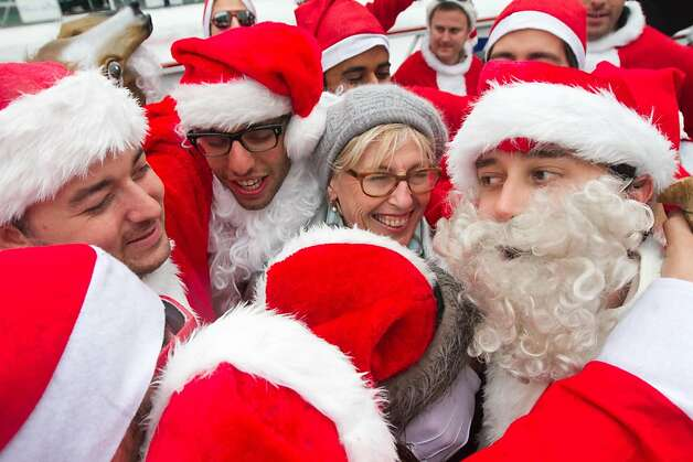 A group of Santas share a group hug with tourist Elizabeth Guerlot of Paris, France at the Santacon event in Union Square on Saturday Dec. 15, 2012 in San Francisco, Calif.  Thousands of revelers, most dressed as Santa Claus, then took off around several city neighborhoods on a holiday inspired pub crawl. Photo: Douglas Zimmerman, SF Gate