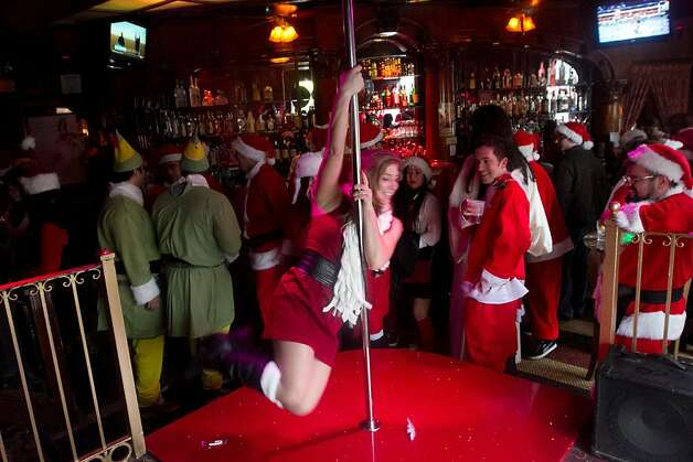 A Santa, who declined to give her real name, uses a dance bar at the Condor Bar in North Beach during Santacon on Saturday Dec. 15, 2012 in San Francisco, Calif.  Thousands of revelers, most dressed as Santa Claus, meet up at Union Square and then took off around several city neighborhoods on a holiday inspired pub crawl. Photo: Douglas Zimmerman, SF Gate