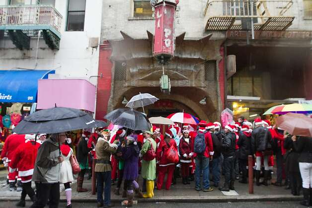 A group of Santacon revelers wait for the Chinatown bar Li Po to open during Santacon on Saturday Dec. 15, 2012 in San Francisco, Calif.  Thousands of revelers, most dressed as Santa Claus, meet up at Union Square and then took off around several city neighborhoods on a holiday inspired pub crawl. Photo: Douglas Zimmerman, SF Gate