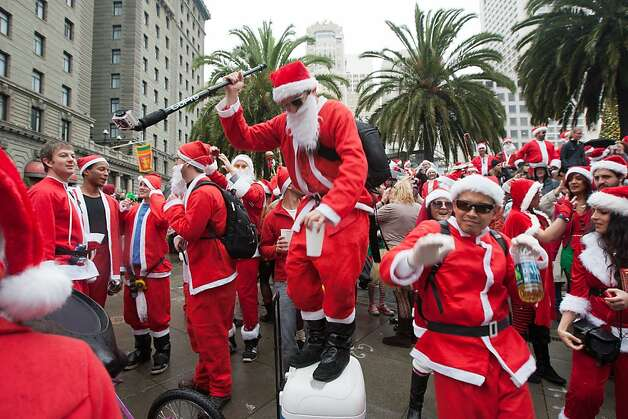 Revelers dressed as Santa Claus dance to some music at the Santacon event in Union Square on Saturday Dec. 15, 2012 in San Francisco, Calif..  Most then took off around several city neighborhoods on a holiday inspired pub crawl. Photo: Douglas Zimmerman, SF Gate
