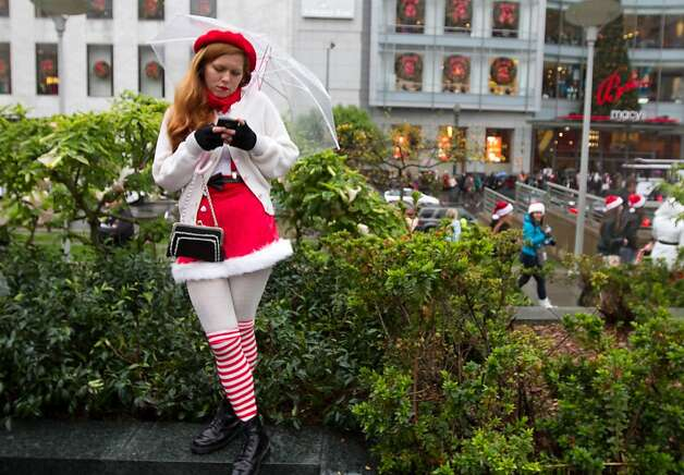Janelle Cruz of San Francisco sends a text while at the Santacon event in Union Square on Saturday Dec. 15, 2012 in San Francisco, Calif.  Thousands of revelers, most dressed as Santa Claus, then took off around several city neighborhoods on a holiday inspired pub crawl. Photo: Douglas Zimmerman, SF Gate
