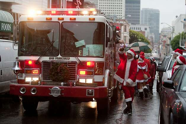 A Santa, hi-fives a San Francisco fireman on Grant Street in North Beach during Santacon on Saturday Dec. 15, 2012 in San Francisco, Calif.  Thousands of revelers, most dressed as Santa Claus, meet up at Union Square and then took off around several city neighborhoods on a holiday inspired pub crawl. Photo: Douglas Zimmerman, SF Gate