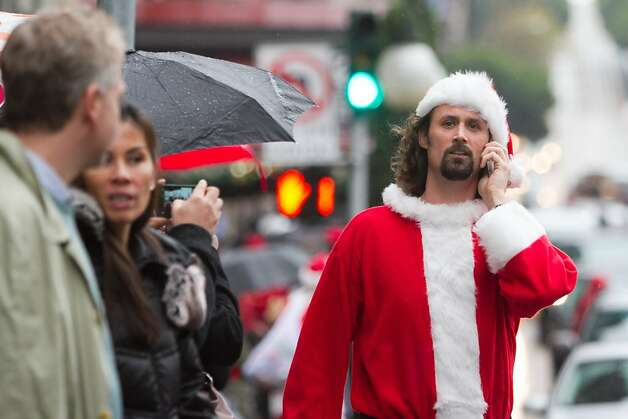 Chris Long of Berkeley, dressed in a Santa suit, tries to find some friends along Powell Street near Union Square during the Santacon event on Saturday Dec. 15, 2012 in San Francisco, Calif.  Thousands of revelers, most dressed as Santa Claus, then took off around several city neighborhoods on a holiday inspired pub crawl. Photo: Douglas Zimmerman, SF Gate