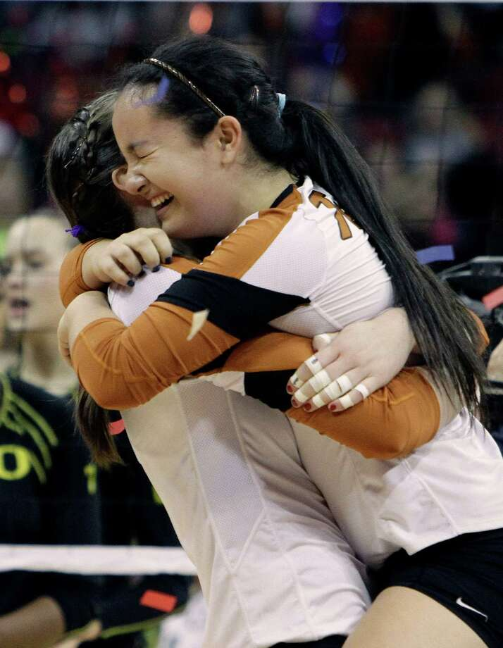 Texas freshmen Kat Brooks, right, and Molly McCage hug after a three-set victory over Oregon in the finals of the NCAA college women's volleyball tournament in Louisville, Ky., Saturday, Dec. 15, 2012. (AP Photo/Garry Jones) Photo: Garry Jones, Associated Press / FR50389 AP