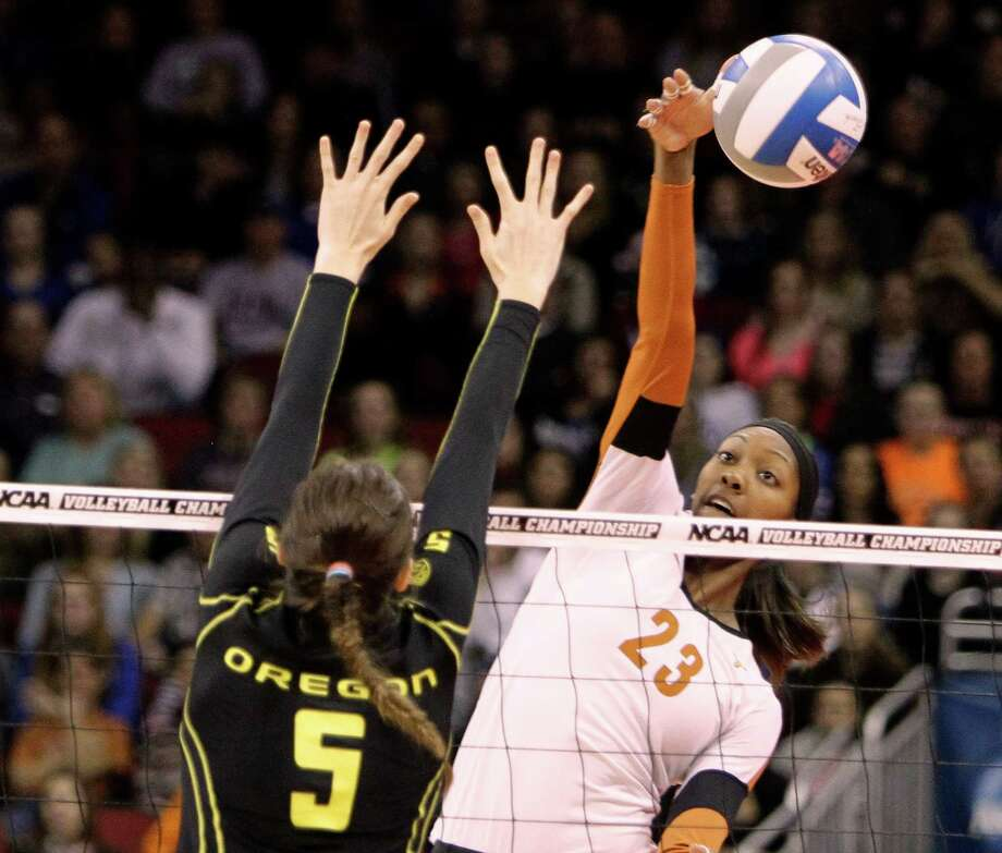 Texas junior Bailey Webster (23) directs the spike around the block attempt by Oregon's Canace Finley (5) during the finals of the NCAA college women's volleyball tournament in Louisville, Ky., Saturday, Dec. 15, 2012.  (AP Photo/Garry Jones) Photo: Garry Jones, Associated Press / FR50389 AP