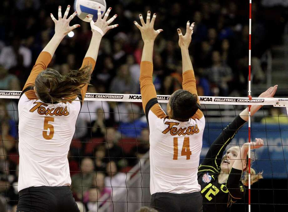 Oregon senior Katherine Fischer (12) tries to spike through the double block by Texas defenders Molly McCage (5) and Sha'Dare McNeal (14) during the finals of the NCAA college women's volleyball tournament in Louisville, Ky., Saturday, Dec. 15, 2012.  (AP Photo/Garry Jones) Photo: Garry Jones, Associated Press / FR50389 AP