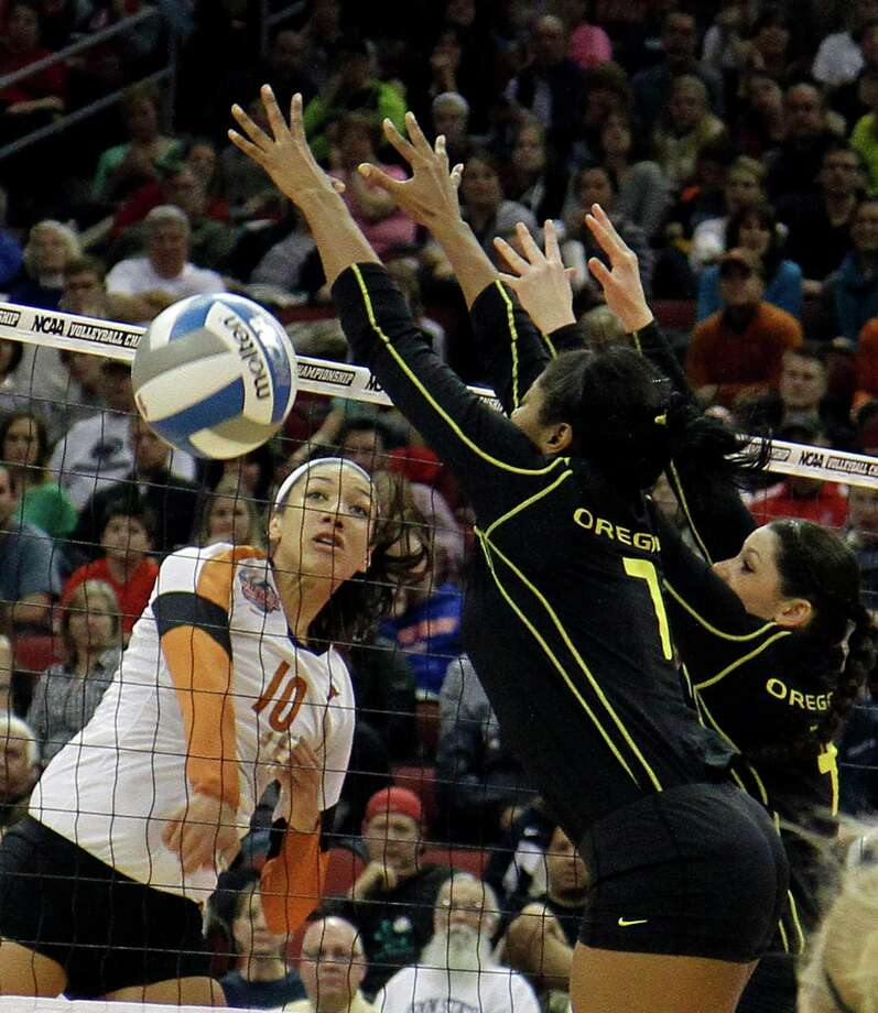 Texas outside hitter Haley Eckerman (10) spikes this shot past the double block-attempt by Oregon's Ariana Williams (7) and Lauren Plum (4) during the finals of the NCAA college women's volleyball tournament in Louisville, Ky., Saturday, Dec. 15, 2012.  (AP Photo/Garry Jones) Photo: Garry Jones, Associated Press / FR50389 AP