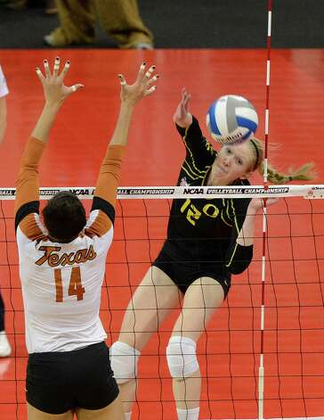 Oregon's Katherine Fischer, right, hits past the defense of Texas' Sha'Dare McNeal during the finals of the NCAA college women's volleyball tournament on Saturday, Dec. 15, 2012, in Louisville, Ky. (AP Photo/Timothy D. Easley) Photo: Timothy D. Easley, Associated Press / FR43398 AP