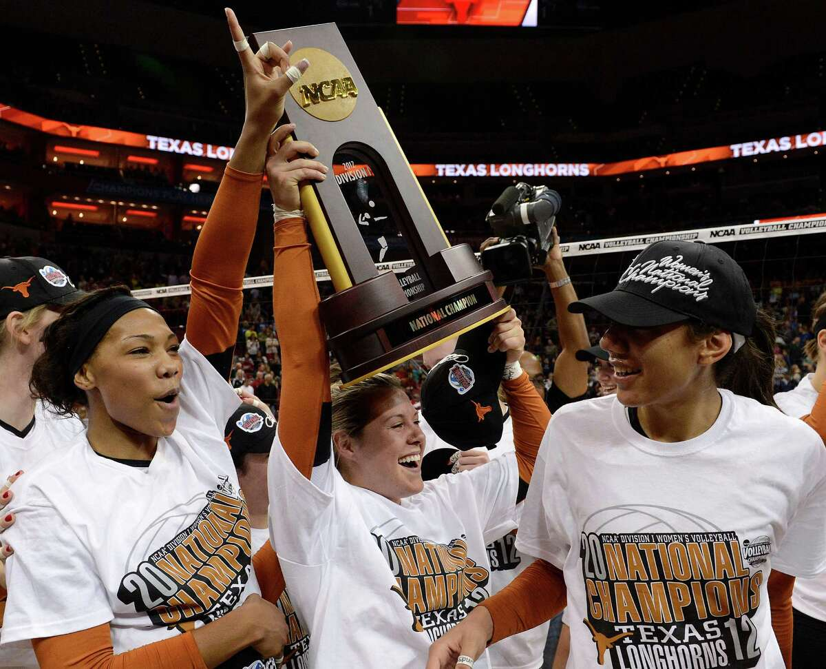 From left, Texas' Khat Bell, Megan Futch, and Halewy Eckerman celebrate with the championship trophy following their victory over Oregon at the NCAA college women's volleyball tournament on Saturday, Dec. 15, 2012, in Louisville, Ky. (AP Photo/Timothy D. Easley)