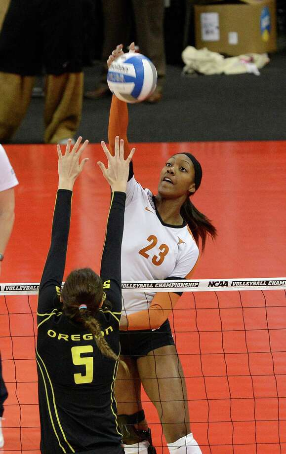 Texas' Bailey Webster (23) hits the ball over the defense of Oregon Canace Finley during the finals of the NCAA college women's volleyball tournament on Saturday, Dec. 15, 2012, in Louisville, Ky. (AP Photo/Timothy D. Easley) Photo: Timothy D. Easley, Associated Press / FR43398 AP