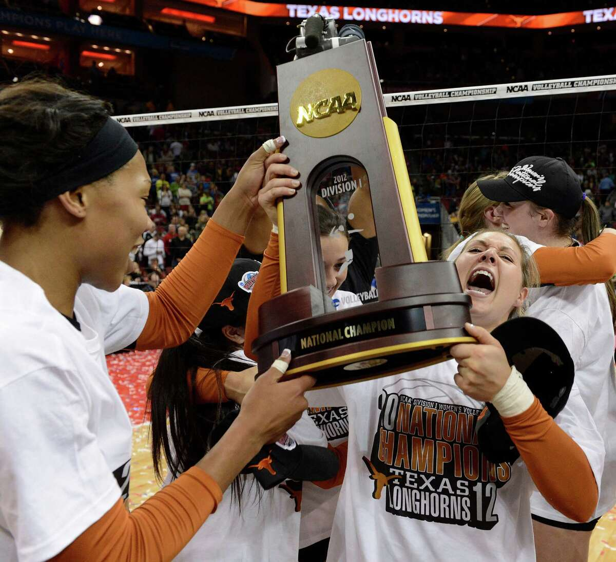 CORRECTS TO KHAT BELL NOT BAILEY WEBSTER - Texas' Megan Futch, right, and Khat Bell, left, raise the championship trophy after their victory over Oregon during the NCAA college women's volleyball tournament on Saturday, Dec. 15, 2012, in Louisville, Ky. (AP Photo/Timothy D. Easley)