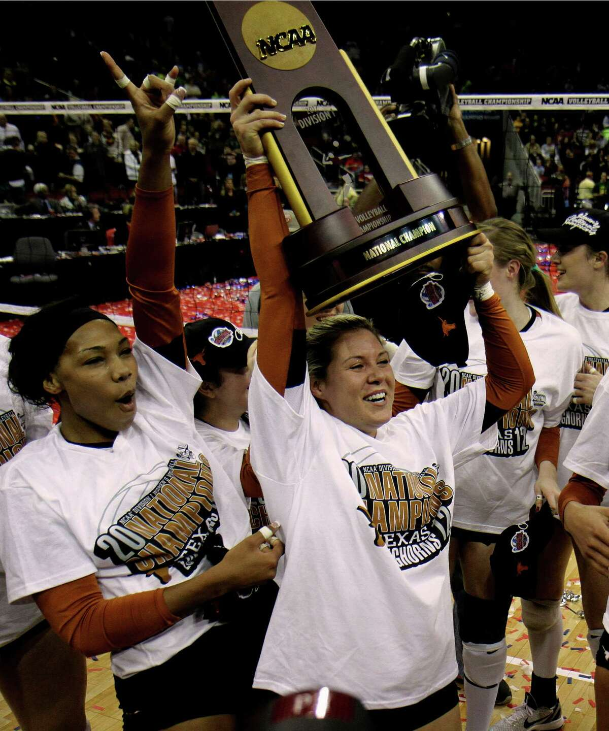 Texas junior Sarah Palmer hoists the trophy after defeating Oregon in the finals of the NCAA college women's volleyball tournament over Oregon in Louisville, Ky., Saturday, Dec. 15, 2012. Khat Bell, left, reacts. (AP Photo/Garry Jones)