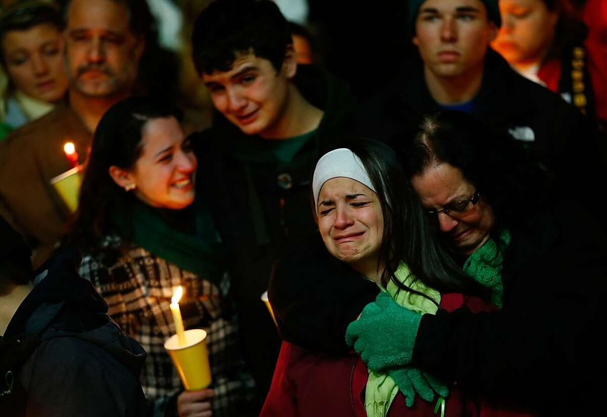 STRATFORD, CT - DECEMBER 15: Donna Soto (R), mother of Victoria Soto, the first-grade teacher at Sandy Hook Elementary School who was shot and killed while protecting her students, hugs her daughter Karly (second from right) while mourning their loss with Victoria's other two siblings, Jillian (far left) and Matthew Soto (second from left), at a candlelight vigil at Stratford High School on December 15, 2012 in Stratford, Connecticut. Twenty-six people were shot dead, including twenty children, after a gunman identified as Adam Lanza opened fire in the school. Lanza also reportedly had committed suicide at the scene. A 28th person, believed to be Nancy Lanza was found dead in a house in town, was also believed to have been shot by Adam Lanza. (Photo by Jared Wickerham/Getty Images)