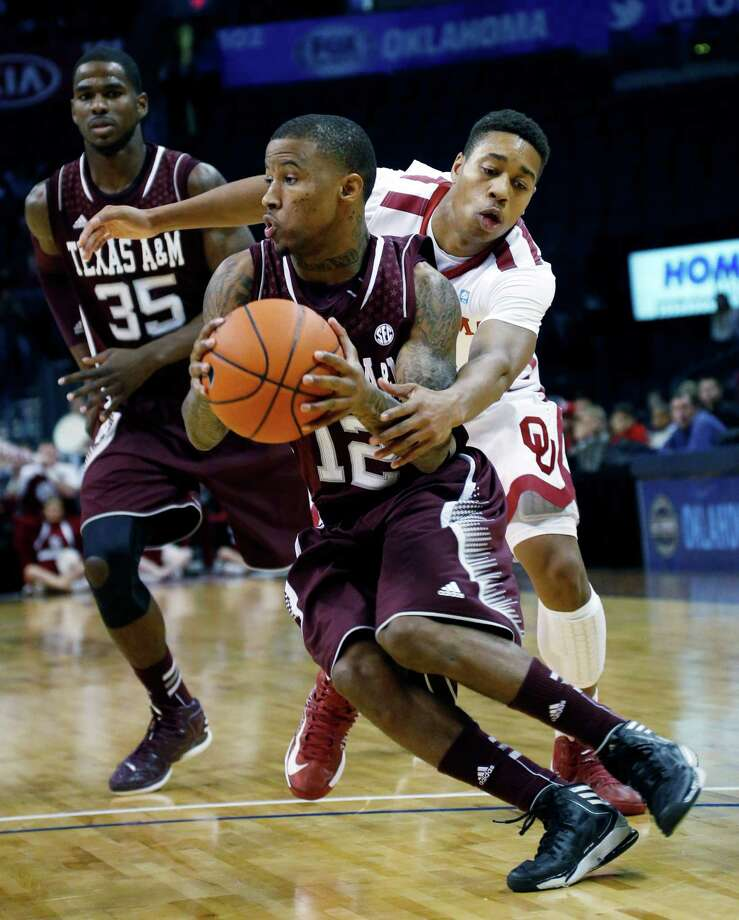 Oklahoma's Isaiah Cousins (11) reaches in to try to knock the ball away from Texas A&M's Fabyon Harris (12) in the first half of Saturday's game. Photo: Sue Ogrocki, STF / AP