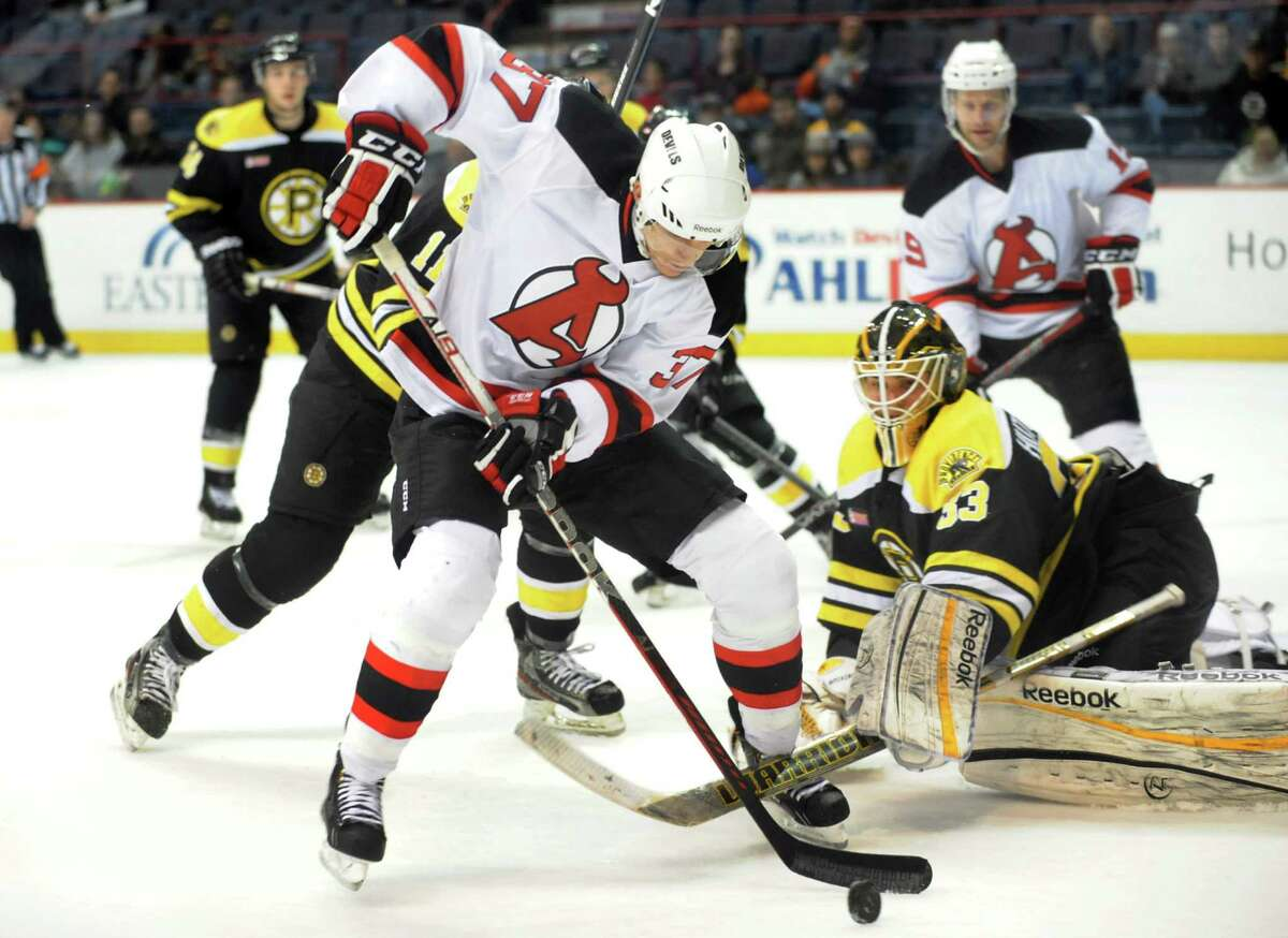 Devils' Chris McKelvie (37), center, works the puck as Bruins goalie Michael Hutchinson (33), right, guards the net during their hockey game on Saturday, Dec. 15, 2012, at Times Union Center in Albany, N.Y. (Cindy Schultz / Times Union)