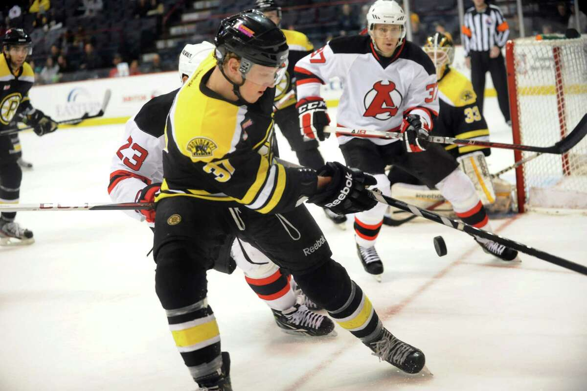 Bruins' Zach Trotman (37), center, and Devils' Chris McKelvie (37), right, pursue a loose puck during their hockey game on Saturday, Dec. 15, 2012, at Times Union Center in Albany, N.Y. (Cindy Schultz / Times Union)