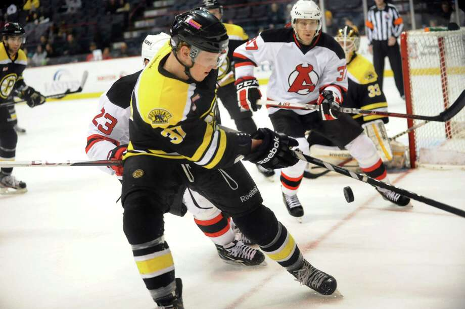 Bruins' Zach Trotman (37), center, and Devils' Chris McKelvie (37), right, pursue a loose puck during their hockey game on Saturday, Dec. 15, 2012, at Times Union Center in Albany, N.Y. (Cindy Schultz / Times Union) Photo: Cindy Schultz / 00020442A
