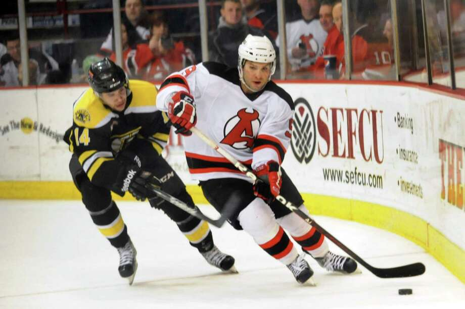 Devils' Joe Whitney (9), right, guides the puck behind the net as Bruins' Craig Cunningham (14) defends during their hockey game on Saturday, Dec. 15, 2012, at Times Union Center in Albany, N.Y. (Cindy Schultz / Times Union) Photo: Cindy Schultz / 00020442A