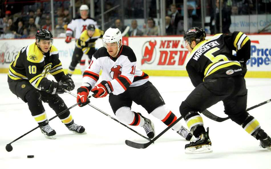 Devils' Bobby Butler (11), center, slices through Bruins' defenders Kyle MacKinnon (10), left, and D