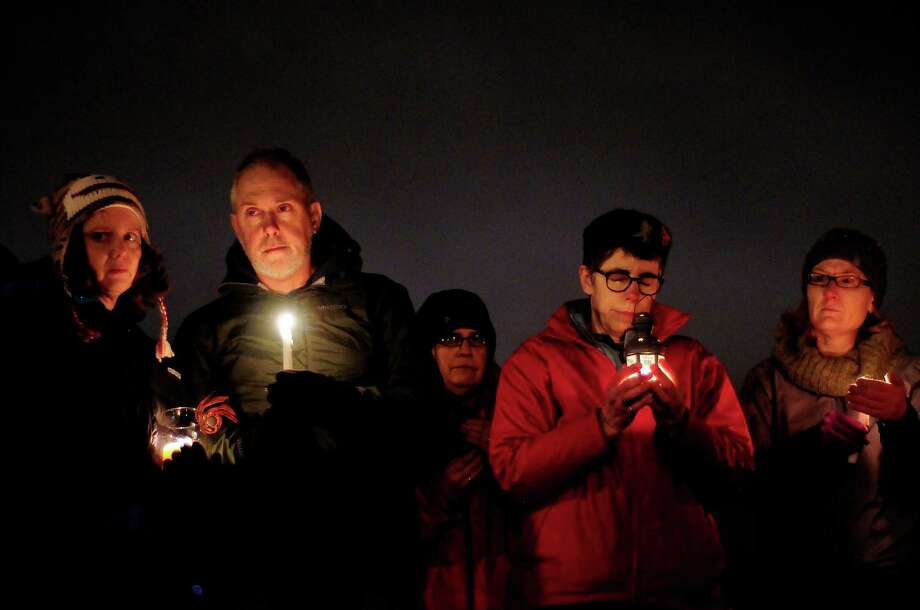 People hold candles in silence during a vigil in remembrance of the Newtown, Conn. shooting victims at Green Lake Park in Seattle on Saturday, December 15, 2012. The vigil was held after a gunman killed his mother and then killed 20 children and six adults at Sandy Hook Elementary in Connecticut before taking his own life. Photo: LINDSEY WASSON / SEATTLEPI.COM