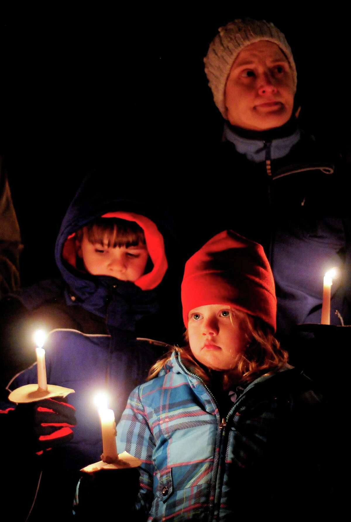 A family holds candles during a vigil in remembrance of the Newtown, Conn shooting victims at Green Lake Park in Seattle on Saturday, December 15, 2012. The vigil was held after a gunman killed his mother and then killed 20 children and six adults at Sandy Hook Elementary in Connecticut before taking his own life.