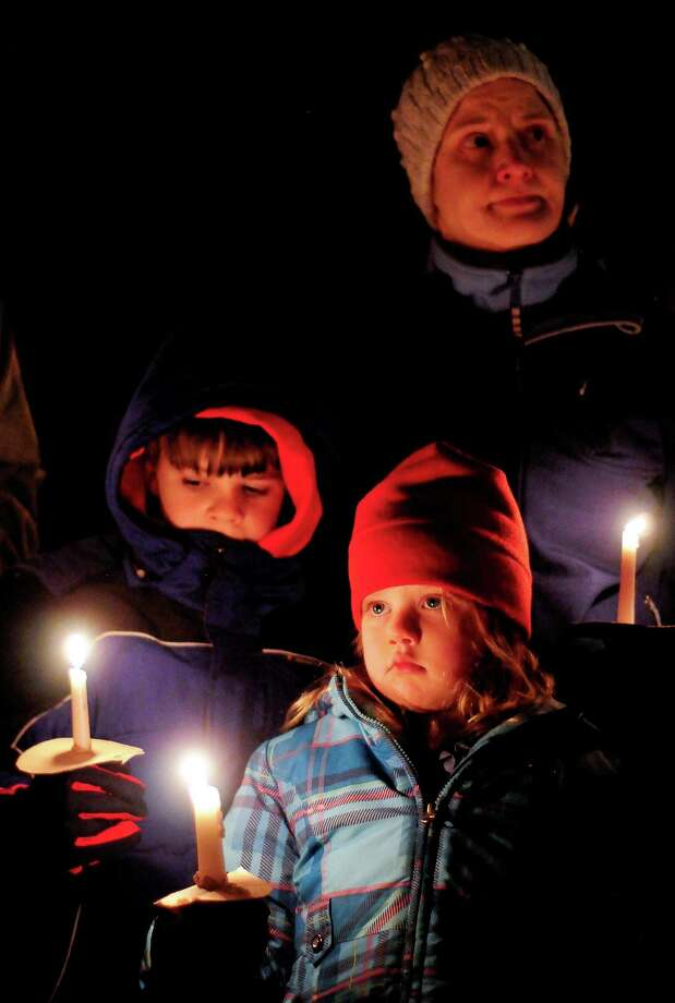A family holds candles during a vigil in remembrance of the Newtown, Conn shooting victims at Green Lake Park in Seattle on Saturday, December 15, 2012. The vigil was held after a gunman killed his mother and then killed 20 children and six adults at Sandy Hook Elementary in Connecticut before taking his own life. Photo: LINDSEY WASSON / SEATTLEPI.COM