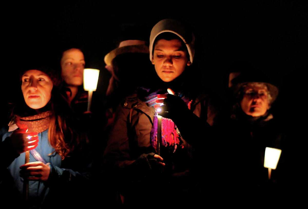 People shield their candles from the wind and light rain during a candlelight vigil in remembrance of the Newtown, Conn. shooting victims at Green Lake Park in Seattle on Saturday, December 15, 2012. The vigil was held after a gunman killed his mother and then killed 20 children and six adults at Sandy Hook Elementary in Connecticut before taking his own life.