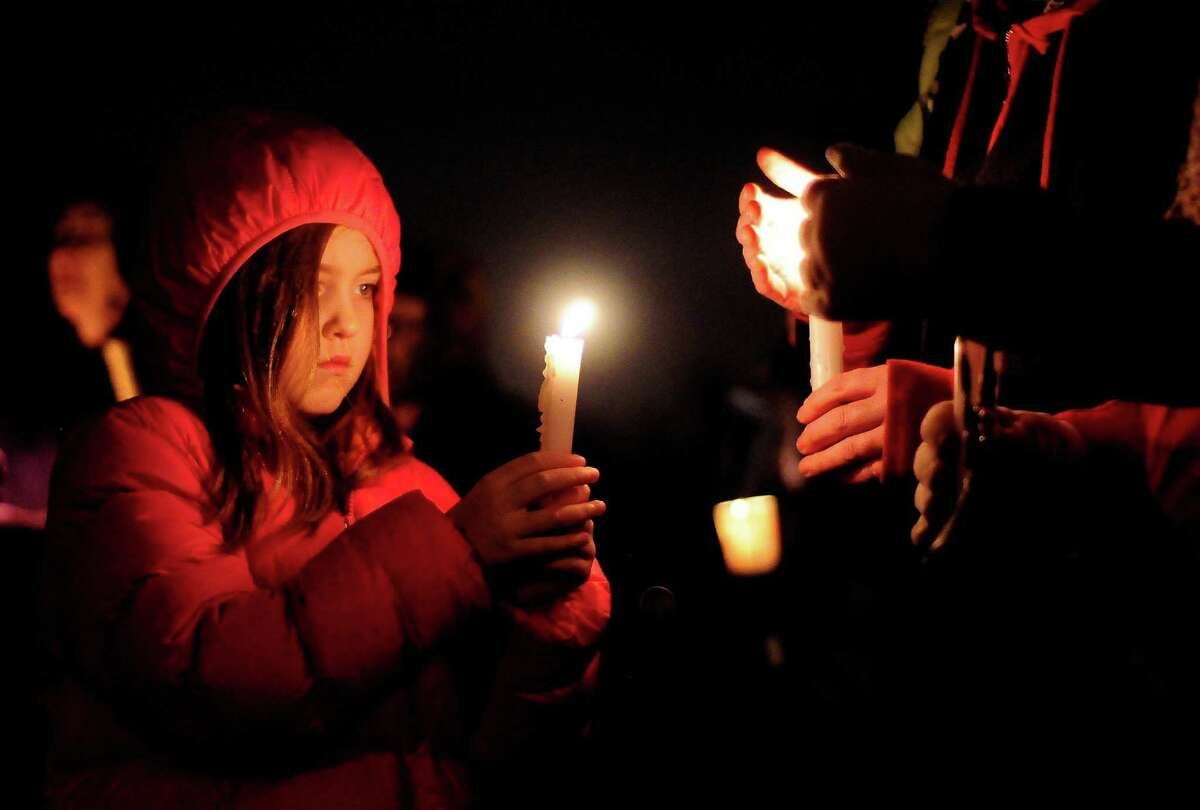 Madeline Slota, 8, holds a candle during vigil in remembrance of the Newtown, Conn. shooting victims at Green Lake Park in Seattle on Saturday, December 15, 2012. The vigil was held after a gunman killed his mother and then killed 20 children and six adults at Sandy Hook Elementary in Connecticut before taking his own life.