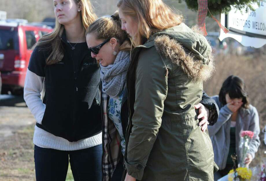 Support is given to a woman who came from out of town to pay her respects, Saturday, Dec. 15, 2012, to the 26 victims of yesterday's tragic shooting at Sandy Hook Elementary School in Newtown, Conn.  (Will Waldron / Times Union) Photo: Will Waldron