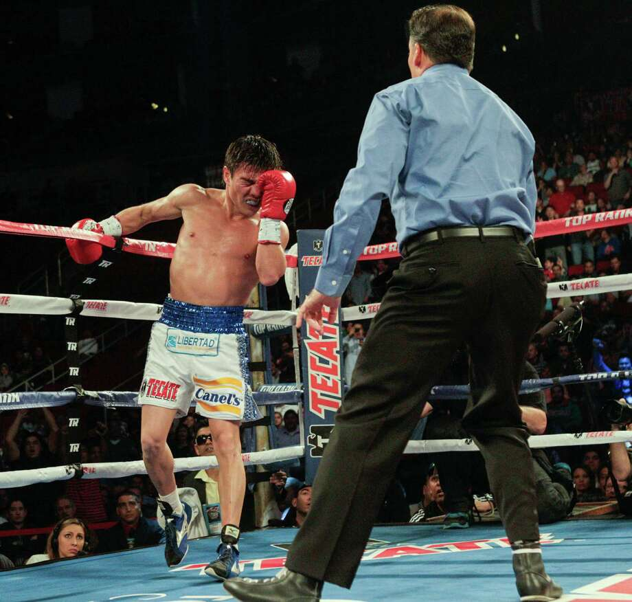 Jorge Arce struggles to get up after being knocked down by Nonito Donaire in the third round as referee Laurence Cole administers a standing eight count during a fight for the WBO Super Bantamweight championship, Saturday, December 15, 2012 in Houston, Texas.Donaire won in the third round by TKO. Photo: Bob Levey, Houston Chronicle / ©2012Bob Levey