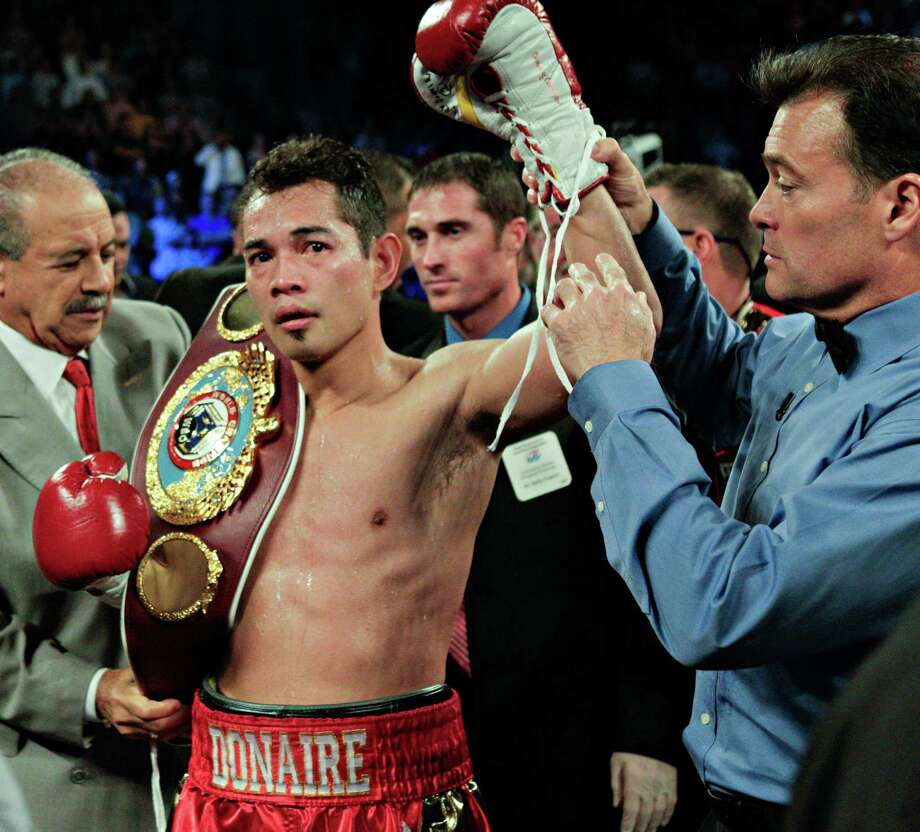 Nonito Donaire has his hand raised by referee Laurence Cole after knocking out Jorge Arce in the third round for the WBO Super Bantamweight championship, Saturday, December 15, 2012 in Houston, Texas. Photo: Bob Levey, Houston Chronicle / ©2012Bob Levey