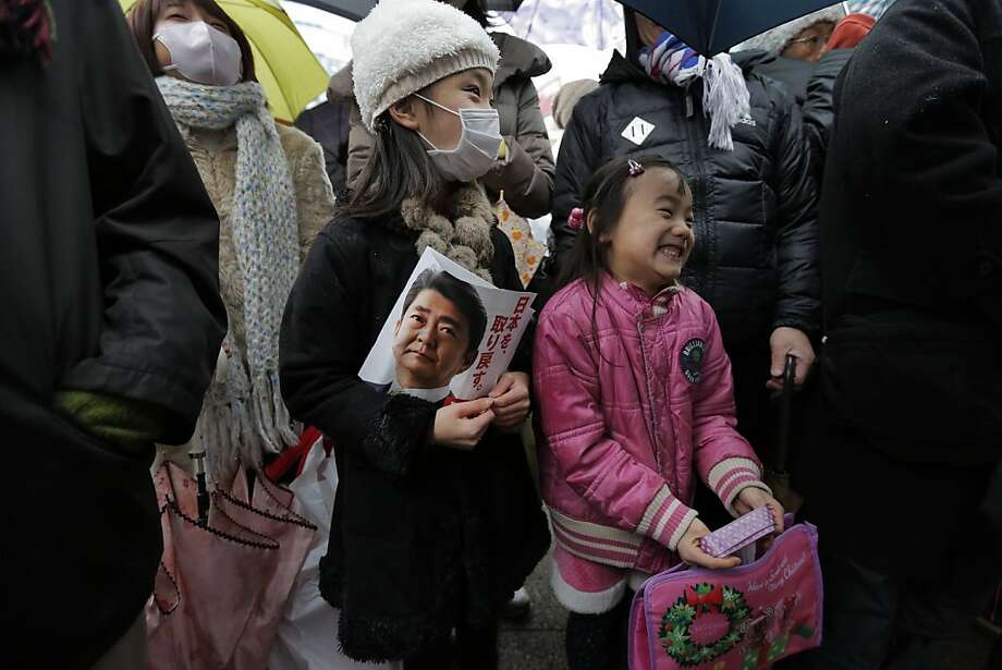 Children chuckle during a speech by Japan's main opposition Liberal Democratic Party (LDP) President Shinzo Abe during a campaign rally for the Dec. 16 parliamentary elections in Kawaguchi, near Tokyo, Saturday, Dec. 15, 2012. Candidates made final impassioned appeals Saturday to voters a day before Japanese parliamentary elections that are likely to hand power back to a conservative party that ruled the country for most of the post-war era. (AP Photo/Itsuo Inouye) Photo: Itsuo Inouye, Associated Press