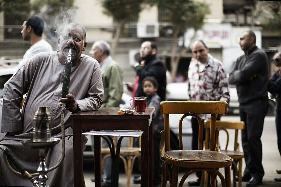 An Egyptian man smokes a waterpipe, known locally as Shisha, as others queue outside a polling station in central Cairo to cast their votes on a new constitution supported by the ruling Islamists but bitterly contested by a secular-leaning opposition on December 15, 2012. President Mohamed Morsi cast his ballot in a polling station close to his presidential palace in the capital, state television showed, but he made no comment to the media. MARCO LONGARI/AFP/Getty Images Photo: Marco Longari, AFP/Getty Images