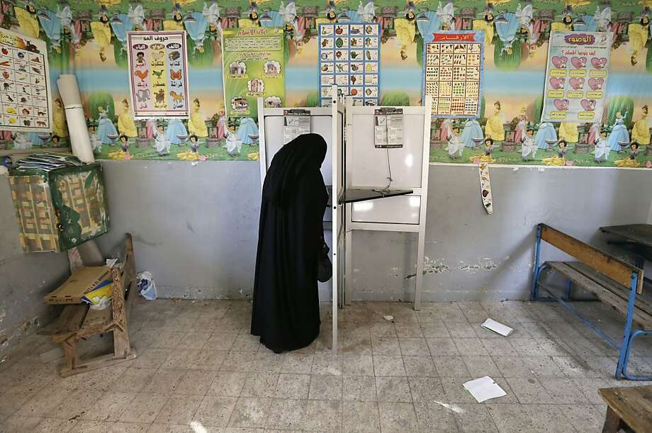 An Egyptian woman casts her vote at polling center during a referendum on a disputed constitution drafted by Islamist supporters of President Mohammed Morsi, in Alexandria, Egypt, Saturday, Dec. 15, 2012. (AP Photo/Hassan Ammar) Photo: Hassan Ammar, Associated Press