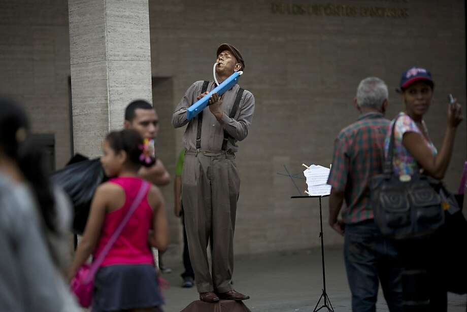 A street artist plays an instrument as he impersonates a mannequin, one day before state elections for governors and legislators, in Caracas, Venezuela, Saturday, Dec. 15, 2012. If candidates who support Venezuela's President Hugo Chavez gain or even hold steady Sunday, the executive branch could strengthen its hold on the grass roots, as communal councils decide, often based on loyalty, such questions as who gets a new roof, or who receives vocational training, distributing the funds directly. (AP Photo/Ariana Cubillos) Photo: Ariana Cubillos, Associated Press