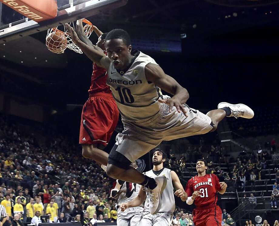 Oregon's Johnathan Loyd, right, flies through the air as Nebraska's Ray Gallegos stuffs the ball in the first half of their NCAA college basketball game in Eugene, Ore., Saturday Dec. 15, 2012. Loyd was trying to block Gallego's shot. Oregon defeated Nebraska 60-38. (AP Photo/The Register-Guard, Kevin Clark) Photo: Kevin Clark, Associated Press