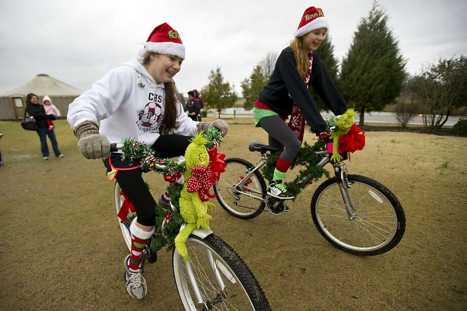 "Rainy weather doesn't bother Ashton White, 14, left, and Lauren South, 14, as they pedal away on their bicycles, decorated with tinsel and Grinch dolls, at the start of the Jingle Bell Ride for Arthritis at Shelby Farms Park in Memphis, Tenn, Saturday, Dec. 15, 2012. The event, benefiting the Arthritis Foundation, offered riders a choice of either a 13 mile route or a five mile ""family ride"" around the park and along the Wolf River Greenway. (AP Photo/The Commercial Appeal, Brandon Dill) Photo: Brandon Dill, Associated Press"